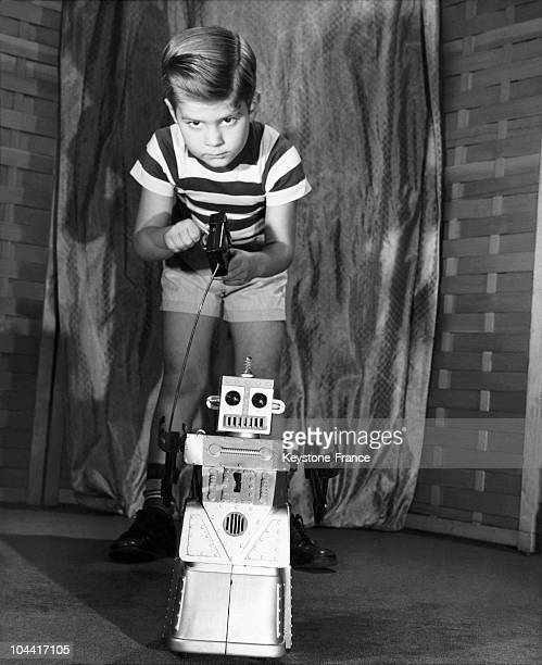 Children playing with one of the first robots that talk walk and whose eyes light up between 1955 and 1965