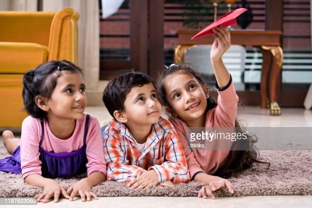 kinder spielen zu hause mit papierflugzeug - kindertag stock-fotos und bilder