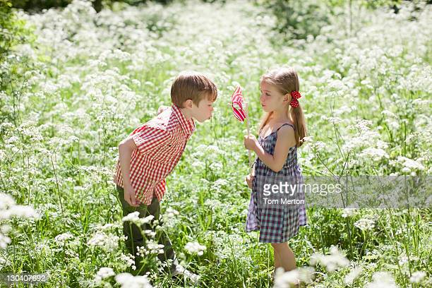 Kinder spielen mit Windrad in Feld mit Blumen