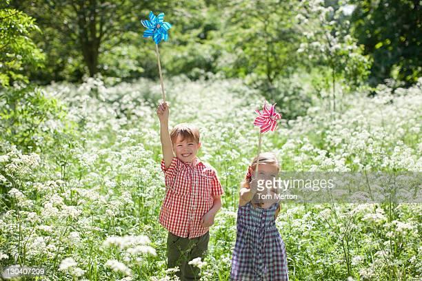 Kinder spielen mit Windrädchen im Bereich der Blumen