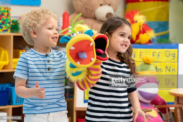 children playing with puppets in classroom - puppet show stock photos and pictures