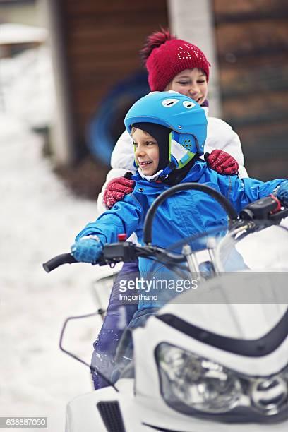 children playing with snowmobile - snowmobiling - fotografias e filmes do acervo