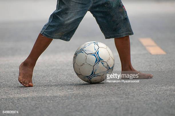 Children playing with soccer ball on road