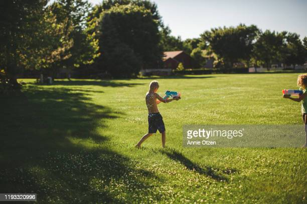 children playing with squirt guns - annie sprinkle stock pictures, royalty-free photos & images