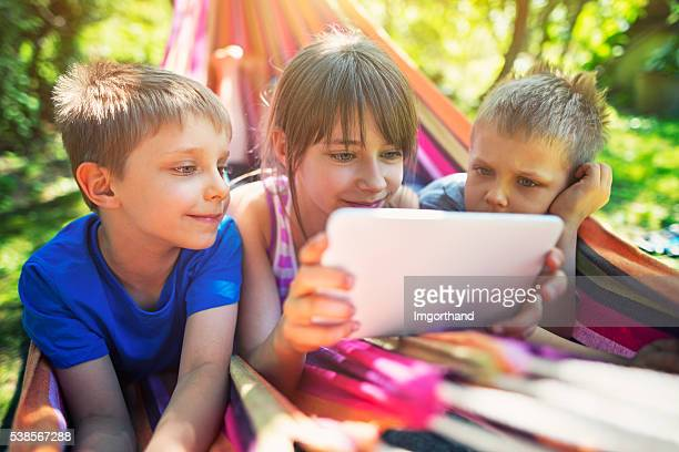 Children playing with tablet on hammock