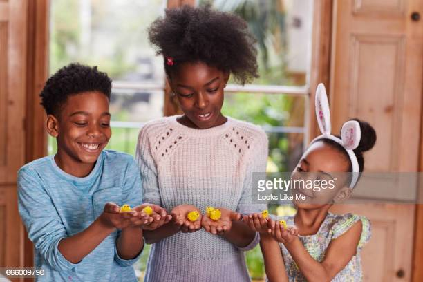Children playing with toy Easter chicks.