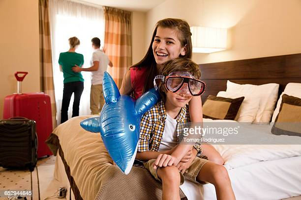 Children playing with toy in hotel room.
