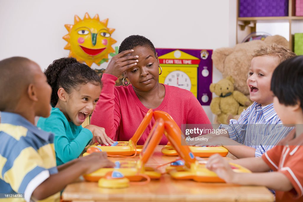 Children playing with toy laptops in class : Stock Photo