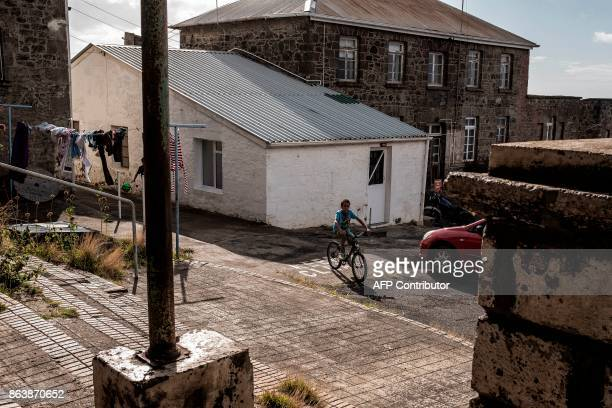A children plays in the backyard of Ladder's Hill fort houses on October 20 2017 in Saint Helena a British Overseas Territory in the South Atlantic...