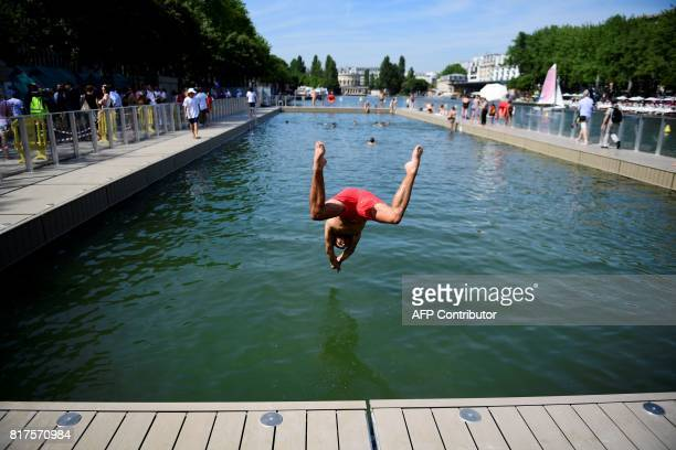 Children plunge in water in a swimming pool at the Bassin de la Villette in Paris on July 18 as part of the Paris Plages summer event / AFP PHOTO /...