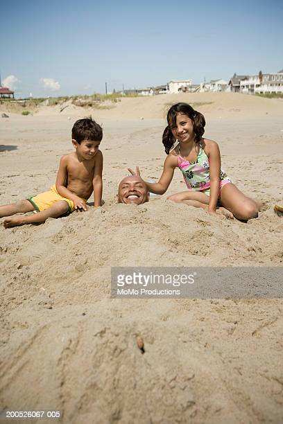 children (4-10)  poking fun at father buried in sand at beach - buried stock pictures, royalty-free photos & images