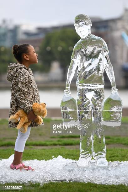Children pose by ice sculptures depicting people collecting water by charity Water Aid to show the fragility of water and the threat posed by climate...