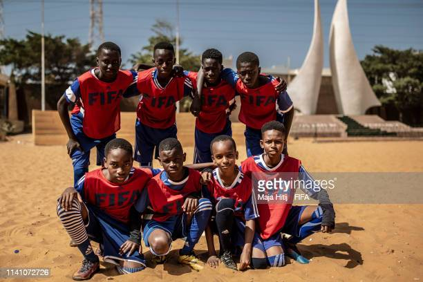 Children pose for a group picture before playing football during a FIFA Grassroots schools program on January 16 2019 in Dakar Senegal
