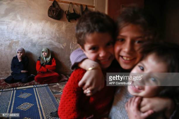 Children pose for a photo as members of the family of Umm Saeed gather in their house on November 6, 2017 in Saqba, in the besieged rebel-held...
