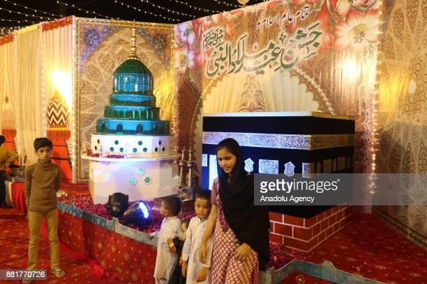Children pose for a photo in front of the models of MasjideNabawi and KhanaeKaba as a street is illuminated with colourful decoration lights for the...