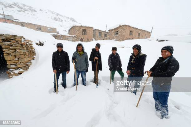 Children pose for a photo on snow covered area after heavy snowfall during winter season in Yukari Narlica village of Catak district in Turkey's...