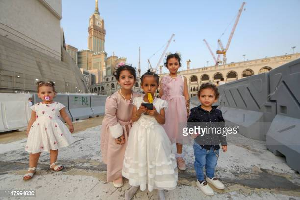 Children pose for a picture after the Eid al-Fitr prayer at the Grand Mosque in the Saudi holy city of Mecca on June 4, 2019. - Muslims worldwide...
