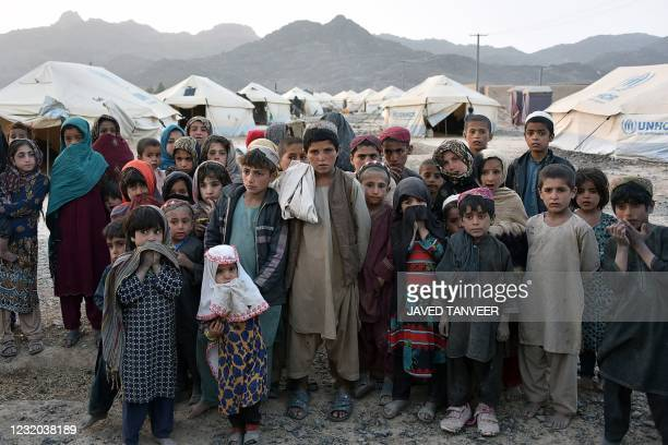 Children pose for photographs in front of their tents at a camp for internally displaced families in Panjwai district of Kandahar province on March...