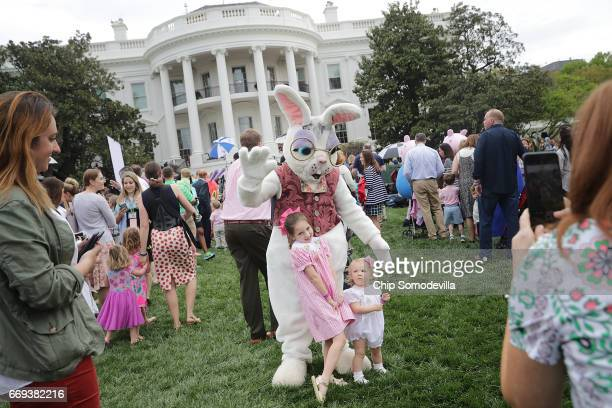Children pose for photographs with one of the costumed Easter Bunny characters during the 139th Easter Egg Roll on the South Lawn of the White House...