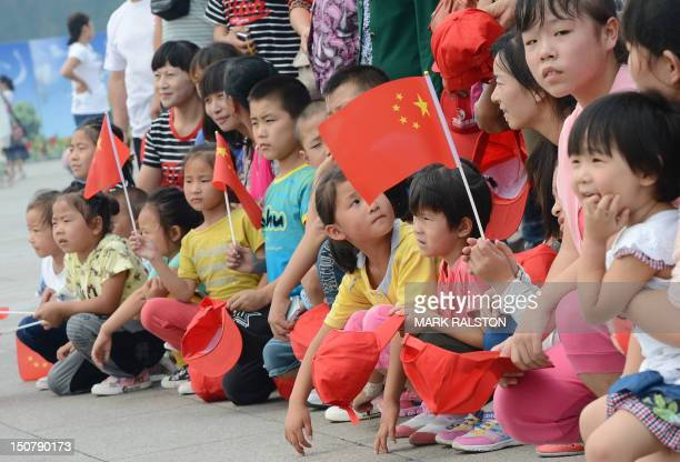 Children pose for photos in Tiananmen Square as the city prepares for the upcoming 18th National Congress of the Communist Party of China that will...