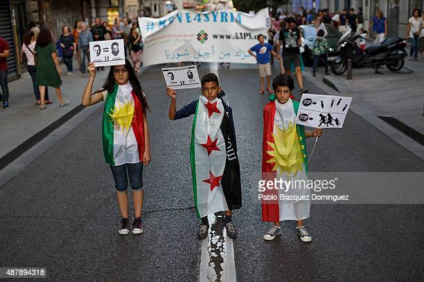 Children pose for pictures as they wear Syrian Independent flag and Kurdistan flag while holding placards reading 'Assad equal to DAESH' during a...