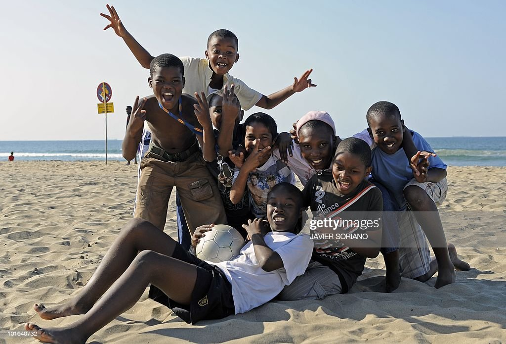 Children pose for the photographer after playing football on a beach in Durban on June 5, 2010. Durban will be one of the nine cities hosting matches of the 2010 World Cup held in South Africa from June 11 to July 11.