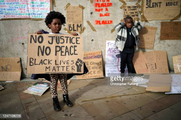 Children pose for their family in front of discarded placards fixed on a wall in Piccadilly Gardens after a Black Lives Matter demonstrations on June...