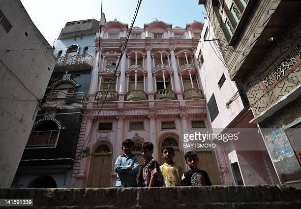 Children pose in front of historical buildings in the old town section of Multan on March 17 2012 Multan one of the oldest cities in the Asian...