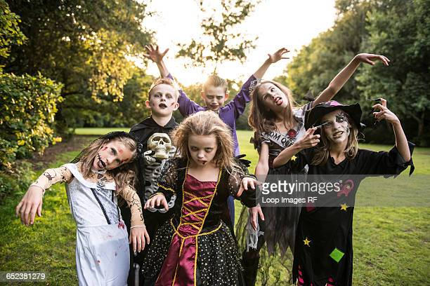 children pose in zombie costumes for halloween night - halloween zombie makeup stock photos and pictures