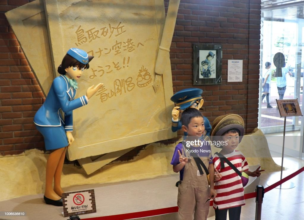 Children pose on July 28 in front of figures of characters