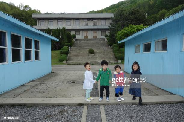 Children pose on the concrete slab that mimics the Military Demarcation Line separating the two Koreas at the Korean Film Council's Namyangju Studios...