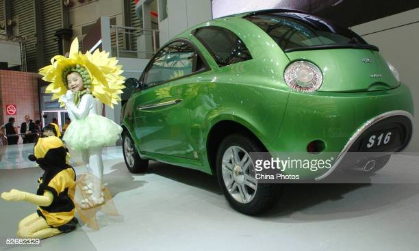 Children pose with a SAIC Chery S16 car at the Auto Shanghai 2005 Exhibition on April 21, 2005 in Shanghai, China. Top world automakers are...