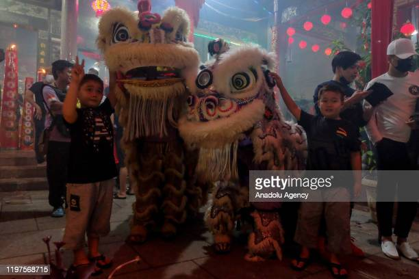 Children pose with lion dance performers during 6th days Chinese New Year celebrations or known as Cue Lak in Selatpanjang Meranti Island Regency...