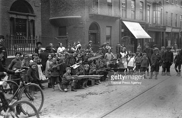 Children pose with pretend weapons in the streets of Dublin influenced by fighting during the Irish Civil War
