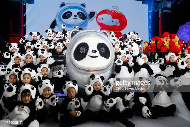 Children pose with the Mascot of the 2022 Olympic Winter Games, Bing Dwen Dwen, during a launching ceremony at the Shougang Ice Hockey Arena on...