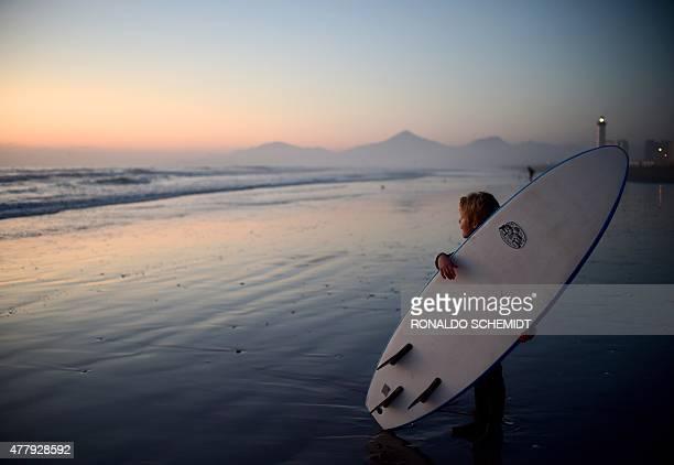 Children practice surfing on a beach in La Serena Chile on June 2015 AFP PHOTO/RONALDO SCHEMIDT