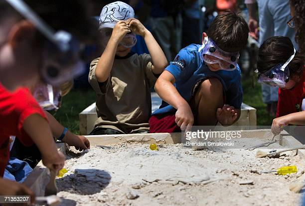Children practice uncovering fossils at an exhibit on paleontology during the 2006 Smithsonian Folklife Festival on the National Mall July 2 2006 in...
