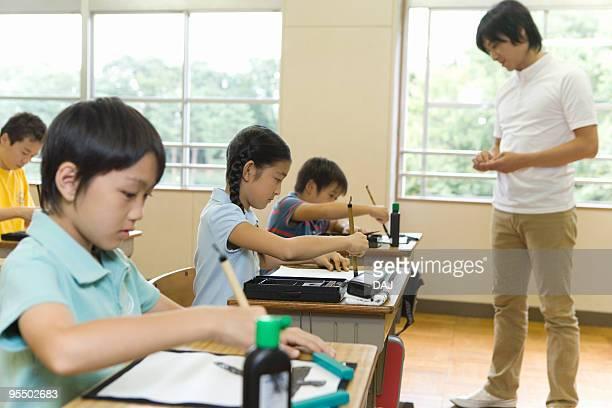 Children practicing calligraphy in classroom