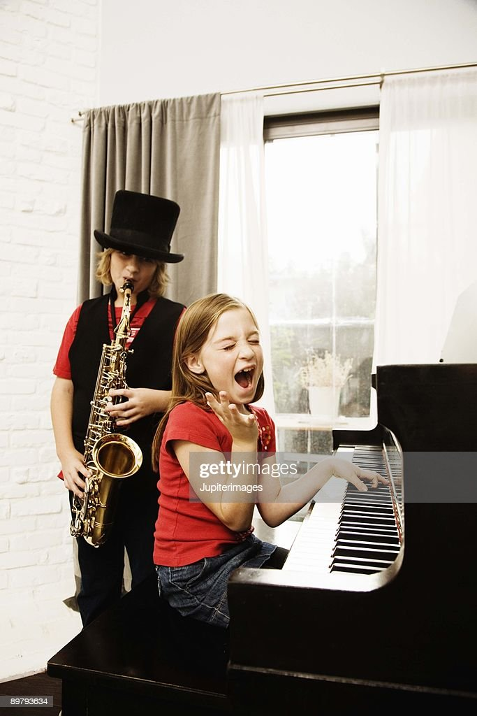 Children practicing on saxophone and piano : Stock Photo