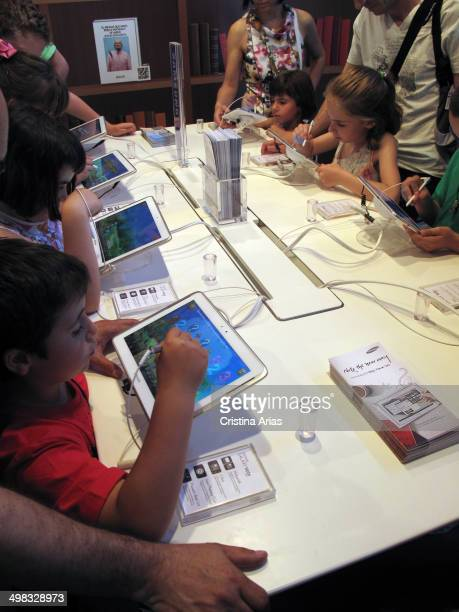 Children practicing with different games and applications on tablets at Book Fair 2013 in Madrid, Spain.