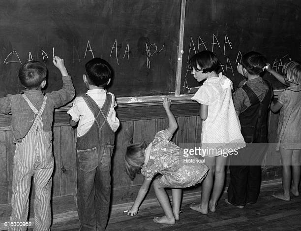 Children practicing writing the letter A on a kindergarten blackboard at Lake Dick a Farm Security Administration project in Jefferson County...