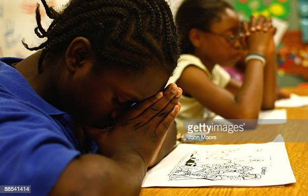 Children pray during scripture study hour at the Center of Hope shelter for homeless women and children on June 16, 2009 in Dallas, Texas. Dozens of...