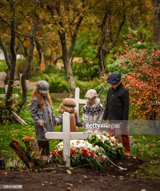 children praying for deceased one. - mourning stock pictures, royalty-free photos & images