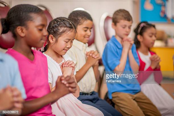 children praying together - christendom stockfoto's en -beelden