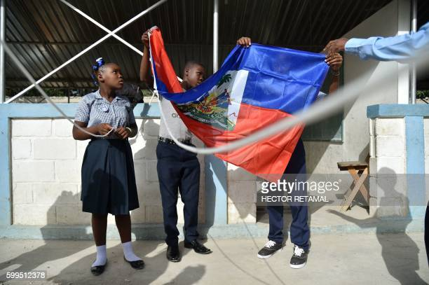 Children prepare to raise the national flag on the first day back to school at the National School of Tabarre in the commune of Tabarre in the...