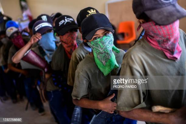 Children prepare to take part in a training demonstration of the Regional Coordinator of Community Authorities vigilante force, in the village of...