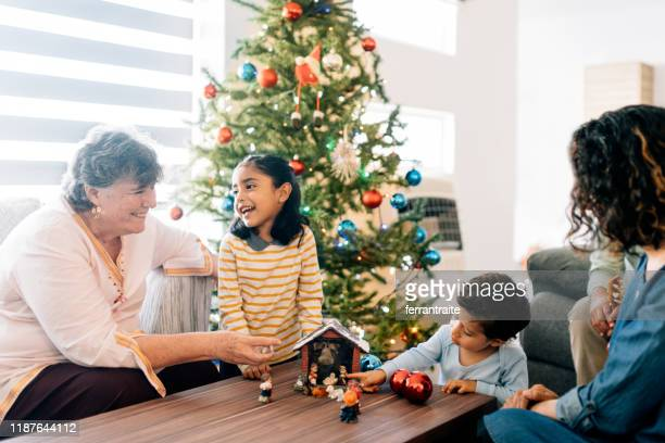children preparing nativity with grandmother - nativity stock photos and pictures