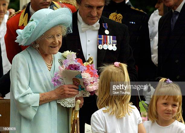 Children present Britain''s Queen Mother with flowers during celebrations to mark her 101st birthday August 4 2001 in London