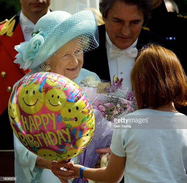 A children presents Britain''s Queen Mother with a balloon for her 101st birthday August 4 2001 in London