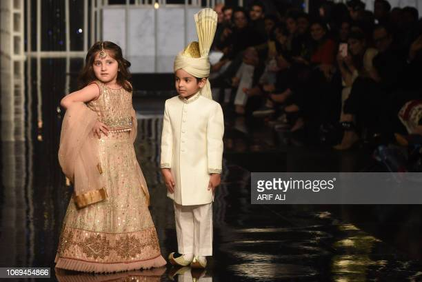 Children presents creations by designer Aisha Imran during the Pantene Hum Bridal Couture Week in Lahore on December 7 2018